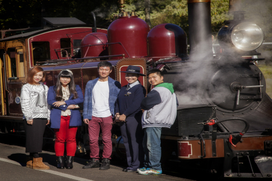 International tourists in front of red loco